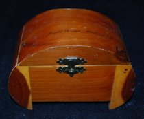 Image of 040.971 - Cedar trinket box given to North Bend High School senior girls by local businesses.  4 1/2 x 21/4 Curved top and sides  The box is made of red cedar and is a souvenir of North Bend High School, Washington. The curved lid closes with a small brass catch. The inside of box has been dugout to form the inside of the box. There are two, small brass hinges on the back.