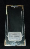 """Image of 951.786 - Greetings, Otto Reinig's Store mirror.                                                                                                                                                                                                                                      Greetings - Otto Reinig.           1902- 1941  4""""x10.125"""" mirror. Corners of mirror have metal frame. Opening in mirror 2.25"""" x 1.625"""" that has greetings from Otto Reinig."""