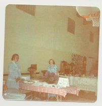 Image of PO.015.0291.g - Antique Show and Sale to benefit Museum held in North Bend Grade School Gym presented by Dick Mattila and his wife. Rita Lessard and Mary Ferrell at museum table to sell cookies, punch and coffee.