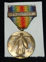 "Image of 003.024 - World War II Victory Medal-WWII medal suspended from ribbon in shades of purple, blue, green, yellow, orange, red, going from red to purple on other side.  Bronze- colored medal approx. 1.5 inches diameter has winged victory on front.  On back has words ""The Great War For Civilization"" with the names of 14 countries involved.  Ribbon has brass bar with word TRANSPORT on it.  Metal and ribbon measures 2.5"" overall. In good condition."