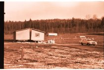 Image of 960.1980.12.13.01.01 - Two mobile homes in a large mostly vacant mobile home park with a car. Trees in background.
