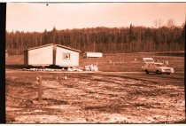 Image of 960.1980.12.13.01.02 - Two mobile homes in a large mostly vacant mobile home park with a car. Trees in background.