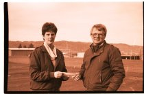 Image of 960.1980.12.13.01.07 - Man and woman holding a check on school sports field.