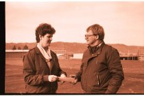 Image of 960.1980.12.13.01.08 - Man and woman holding a check on school sports field.