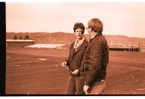 Image of 960.1980.12.13.01.09 - Man and woman holding a check on school sports field.