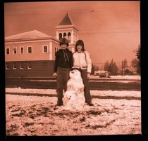 Image of 960.1981.12.28.01.12 - Two young students with snow man at School Administration building.