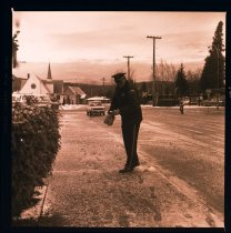 Image of 960.1982.01.04.01.01 - Snoqualmie Police Chief Massey sanding snowy sidewalk outside of River St City Hall.