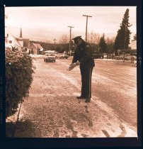 Image of 960.1982.01.04.01.02 - Snoqualmie Police Chief Massey sanding snowy sidewalk outside of River St City Hall.