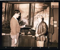 Image of 960.1982.01.04.02.01 - Mayor Charles Peterson giving Charles Smith an award for work on Railroad Park in Snoqualmie City Hall with City Council in background.