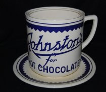 """Image of 092.012 - Edgerly's Drug Store Giant hot chocolate cup sales prop, North Bend.                                                                                                                                                                                                                                       Oversize crockery cup and Saucer (one piece): white with blue band with pointed edge around top of cup and rim of saucer; brand name written on front of cup in blue """"JOHNSTON'S"""" with """"Hot Chocolate"""" printed in blue at bottom of cup, front.   Size: cup: 7.5"""" high x 7"""" diameter at top saucer: 11.5"""" diameter, attached to cup bottom. cup handle- 5"""" opening at cup and 2.5"""" width at top handle  Came from Edgerly's Drug Store, North Bend. Used in 1920s or 1930s."""