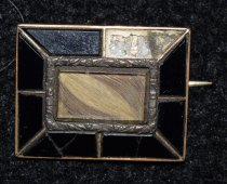 Image of 002.011 - Small, oblong breastpin owned by Euphemia Morehead Rees' grandmother Mrs. Moorehead- Anderson.  Black onyx edge.  Dark hair in center was hers and light hair was her husband's.