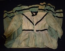Image of 002.002 - Green dress belonging to Mina Kanim Borst, second wife of J.W. Borst, mother of Alice-Borst-Rees-Rachor, mother of Jerry Rees.  Dress in poor condition, faded, with holes. Black velvet ribbon trim of .75""