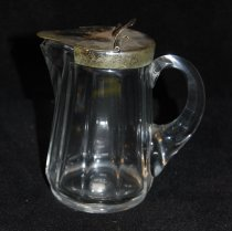 Image of 002.038.2 - Glass syrup pitcher with brass lid from household of Mrs. Lloyd (Euphemia) Rees.