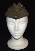 """Image of 044.001.a - Lester Burn's Marine Uniform.  a. Marine Corps Cap, Olive green, with bronze Marine emblem button on front one side. Cap creased throughout upper side flaps loose at top and hooked onto cap by hook in flaps and hand-sewed eye in cap. Lined with heavy cotton material,olive green color.  b. Marine Corps bronze symbol button on front of cap. Left side. Round world globe with maps of No. and So. America on side; Anchor with entwined rope attached to top ring of anchor: Eagle with outspread wings on top of globe.  c. Round screw for attaching marine symbol through cloth of cap.  d. 5/8"""" round bronze button on cap flap, front. Eagle and anchor symbol with stars around upper edge.  e. 5/8"""" round bronze button on cap flap, front: eagle and anchor symbol with stars around upper edge. Horstman, Phila. stamped on back of buttons on flap."""