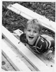 Image of Gabriel Warren outside playing on pile of wood
