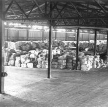 Image of 2009.15.0006-G - A SECTION OF THE TRANSIT SHED AT BERTH 230-E, SHOWING A SHIPMENT OF RAW RUBBER IN THE FOREGROUND, SYNTHETIC RESIN AND BALED ROPE FIBER IN THE BACKGROUND.