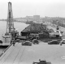 Image of 2009.15.0836-G - LOOKING SOUTHERLY FROM THE ROOF OF THE TRANSIT SHED AT BERTH 90, SHOWING THE DESTRUCTION OF THE WHARF BETWEEN BERTH 86 AND BERTH 88, BY THE FIRE OF MAY 14, 1941.  NOTE THAT THE TEAM FERRY LANDING AT BERTH 88, WHICH WAS PARTIALLY DESTROYED BY THE SAME FIRE, HAS BEEN TEMPORARILY REPAIRED, AND FERRY SERVICE HAS RESUMED.
