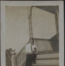 Image of [Man sitting on porch with cat] - Burton family papers and photographs