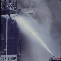 Image of [Firemen entinguishing a fire above a bookstore] - 1977 Blackout Slide collection