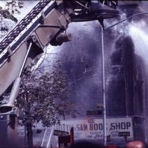 Image of [Extinguishing a fire in the Ruth & Sam Book Shop building] - 1977 Blackout Slide collection