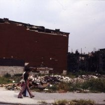 Image of [Pedestrians walk by a yard full of rubble] - 1977 Blackout Slide collection
