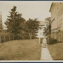 Image of [Shaker Sister Standing Next to the North Family Laundry] - Mount Lebanon, NY