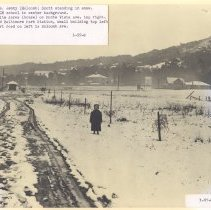 Image of Copy of photo of Holcomb Ave. looking south;  Mrs. Scott as young girl standing center in heavy snowfall.  L-CM school in center background.  White Acres (house) on Monte Vista Ave. top right.  Old Baltimore Park Station, small building top left with signal tower to the left.   Dirt road on left is the old Maryland Ave., now Holcomb Ave.  Photo looks south towards Corte Madera and shows left background top Christmas Tree Hill.