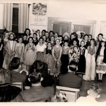 Image of L/CM school play day and anniversary night. large group of performers in fron of audience