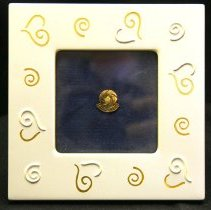 Image of Sun City General - Gold lapel pin with Sun City logo with yellow jewel in center.  Given to residents and employees of Del E. Webb Construction Company.  Deed of gift from Stuart Weinland on 12/13/02.  Photo by Bob McColley.