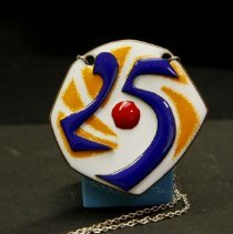 Image of Sun City General - Ceramic 25th Sun City Anniversary pendant made at the Copper Enameling Class at Bell Rec Center by Velma Wilson.  Deed of gift by Velma Wilson on 12/2/09.  Photo by Bob McColley.