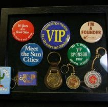 Image of Sun City and Sun City West General - Picture frame with souvenir pins and key chains of Sun City, Sun City West  and Del Webb.  Photo by Bob McColley.