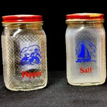 Image of 1960's Household - Glass salt and pepper shakers with red metal lids. Deed of gift from Patricia Lawson on 2/2/06. Photo by Bob McColley. 