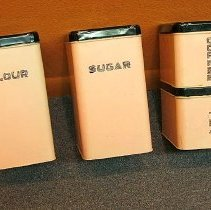 Image of 1960's Household - Four piece pink canister set with black lid, for flour, sugar, coffee and tea.  Deed of gift by Natalie Kleinkauf on 5/1/06.  Photo by Bob McColley.