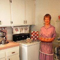Image of 1960's Household - Kenmore washing machine.  Deed of gift by Rose Siegmund on 5/3/05.   Cardboard cutout of 1960 woman in kitchen with necklace and clip-on earrings.    Photo by Bob McColley.   Part of re-creation of 1960 kitchen.