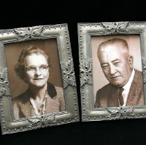 Image of 1960's Household - Two framed pictures of Chloe and John MacDonald,  the first owner residents of 10801 Oakmont Drive.  They purchased the house in 1962, after the home was one of the first models in Sun City and toured for the Opening Weekend on January 1, 1960.  This is where the Sun Cities Area Historical Society Museum is currently located.  Photo by  Bob McColley.