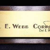 "Image of Del Webb - Del E Webb desk name plate and stand, including his signature and Del E. Webb Corporation. Inscription: ""Del E. Webb Corporation Del E. Webb, Chairman.""  Loaned from Marjorie Johnson, widow of R.H. Johnson on 11/14/09.  Photo by Bob McColley."