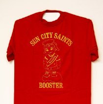 "Image of Sun City General - Red t-shirt in yellow lettering saying ""Sun City Saints Booster"" . Deed of gift by Ed Allen on 12/6/10.  Photo by Bob McColley."