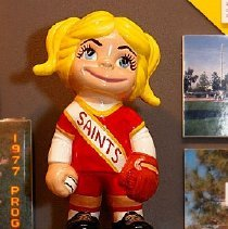 Image of Sun City General - Sun City Saints ceramic doll that was designed and built by Maricopa County detective Bill Kohler and given to the Saints.   Deed of gift from Retha Beveridge on 6/3/92.   Below doll is information regarding the Saints logo.  