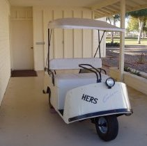 Image of Sun City General - Three wheel 1960-1963 Cushman golf cart.  Golf cart was purchased by Henry and Marie Bartenhagen in 1967 in Sun City as used.   The Bartenhagen family restored the golf cart and presented it to the Sun City Historical Society, to celebrate Sun Cities 50th Anniversary as a gift on 2/2/10.