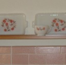 Image of Sun City General - White glass snack set with pink floral design containing 4 trays and 4 cups.  Deed of gift from Essie Mae Albritton on 4/14/11.