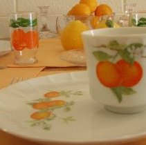Image of Sun City General - Dinner plate and cup with oranges on them.   They are on exhibit during orange season.