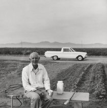 Image of Working in Agricultural Center - Black and white photo of unknown man sitting on a bench at the Agricultural Center