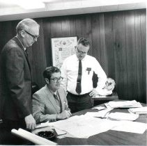 Image of DEVCO Del E. Webb Development Co. - L to R: Owen Childress, John Meeker and Tom Rittenhouse Chief of Operations.  Meeker seated at desk and other two standing looking at plans on desk