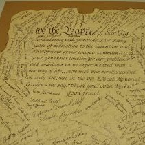 "Image of Del Webb Construction & Corporation - Scroll given to John Meeker states:  ""We the people of Sun City remembering with gratitude your many years of dedication to the invention and development of our unique community, your generous concern for our problems and ambitions as we experimented with a new way of life...now with this scroll, inscribed on July 4, 1987 in the Del E Webb Memorial Garden - we say, thank you, John Meeker."""