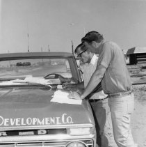 Image of DEVCO field superintendents - Field superintendent Del Martinson checks plans with Gene Smallwood who is superintendent of duplex construction on a 110-degree day.  Photo in Webb Spinner August-September 1974 page 6.