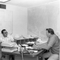 Image of DEVCO construction office - At his desk Del Martinson field superintendent talks with John Clark. On Del's right is a blue print of Sun City, which if continued will progress across the ceiling. Two other walls are covered with blow-up sections where construction is currently underway and Martinon jokes about papering over his windows with maps.  Photo in Webb Spinner August-September 1974 page 7.