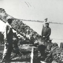Image of Salvaged Cannon with men beside it - Print, Photographic