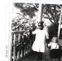 Image of Child with doll in stroller - Print, Photographic
