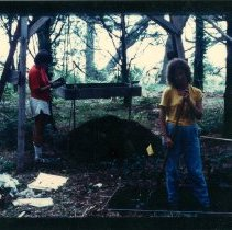 Image of Color print of 2 unknown workers investigating Dorion dig. - Print, Photographic