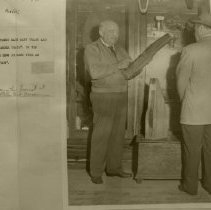 Image of Mr. Decker showing Cypress wood to a visitor to Fort Clnch
